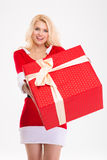 Beautiful woman in santa claus dress giving you red gift Royalty Free Stock Images
