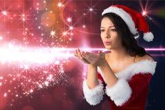 Beautiful woman in santa costume blowing magic dust Stock Images
