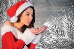 Beautiful woman in santa costume blowing snow Stock Photo
