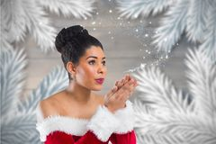 Beautiful woman in santa costume blowing snow flakes. Against digitally generated background during christmas time Stock Photos