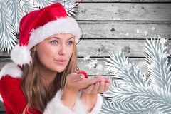 Beautiful woman in santa costume blowing snow flakes. During christmas time Stock Photos