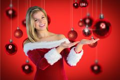 Beautiful woman in santa costume gesturing against digitally generated background Stock Image