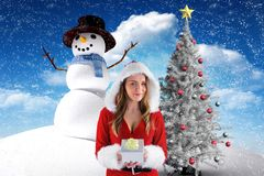 Beautiful woman in santa costume holding a gift against digitally generated background Stock Image