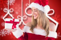 Beautiful woman in santa costume holding a gift Royalty Free Stock Images
