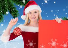 Beautiful woman in santa costume holding red placard and bauble Stock Photo