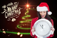 Beautiful woman in santa costume holding wall clock during christmas time Royalty Free Stock Photo