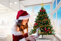 Beautiful woman in santa costume looking at christmas gift. During christmas time Stock Photography