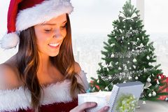Beautiful woman in santa costume looking at gift. During christmas time Stock Images