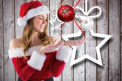Beautiful woman in santa costume pretending to hold a imaginary christmas decoration Royalty Free Stock Photo