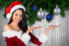Beautiful woman in santa costume showing christmas baubles Stock Images