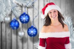 Beautiful woman in santa costume standing against digitally generated background Royalty Free Stock Image