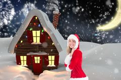 Beautiful woman in santa costume standing against digitally generated background Royalty Free Stock Photography