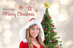 Beautiful woman in santa costume standing near christmas tree. Against digitally generated background Stock Photo