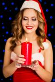 Beautiful woman in Santa dress with candle. Photo of Beautiful woman in Santa dress with candle Royalty Free Stock Photography