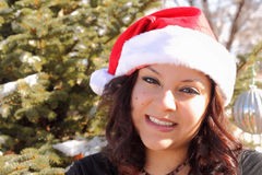 Beautiful Woman with Santa Hat. Image of a beautiful woman wearing a santa hat in front of pine tree Stock Image