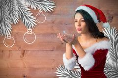 Beautiful woman in santa hat blowing snow. During christmas time Royalty Free Stock Images