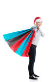 Beautiful woman in santa hat carrying shopping bags. Royalty Free Stock Images