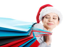 Beautiful woman in santa hat carrying shopping bags. Stock Photo