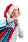 Beautiful woman in santa hat carrying shopping bags. Royalty Free Stock Photos