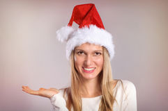 Beautiful woman with a Santa hat gestures palm up. Stock Image