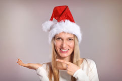 Beautiful woman with a Santa hat gestures palm up. Smiling Christmas girl Stock Photography