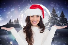 Beautiful woman in santa hat gesturing against digitally generated background Stock Images