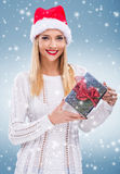 Beautiful woman with santa hat in his hand a gift Stock Image