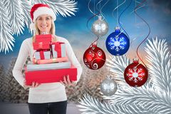 Beautiful woman in santa hat holding christmas gifts Stock Photos