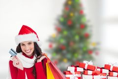 Beautiful woman in santa hat holding credit card and shopping bags. During christmas time Royalty Free Stock Photos