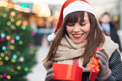 Beautiful woman in santa hat holding present box on christmas ma Royalty Free Stock Photo