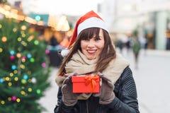 Beautiful woman in santa hat holding present box on christmas ma Stock Photos