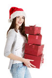 Beautiful woman in santa hat holding presents. Stock Photos