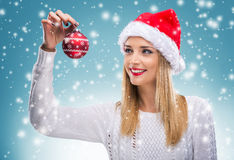 Beautiful woman with santa hat holding red Christmas Ornament Royalty Free Stock Photos