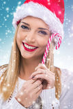 Beautiful woman with santa hat holding red -white Christmas Lollipop Stock Photo