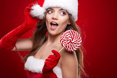 Beautiful woman with santa hat holding red -white lollipop Stock Images