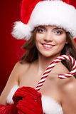 Beautiful woman with santa hat holding red -white lollipop Royalty Free Stock Photo