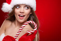 Beautiful woman with santa hat holding red -white lollipop Royalty Free Stock Photos