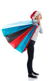 Beautiful woman in santa hat holding shopping bags. Royalty Free Stock Photo