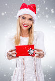 Beautiful woman with santa hat holding a small red gift box Stock Image