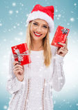 Beautiful woman with santa hat, holding two red gift box - snowfall Stock Photography