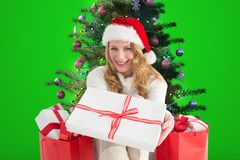 Beautiful woman in santa hat offering a christmas gift. Against digitally generated background Stock Photos