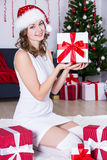 Beautiful woman in santa hat sitting near decorated Christmas tr Royalty Free Stock Photography