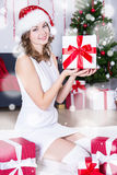 Beautiful woman in santa hat sitting near decorated Christmas tr Royalty Free Stock Images