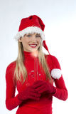 Beautiful woman in santa's hat holding a candle. Beautiful young woman in santa's hat holding a red candle Royalty Free Stock Photos