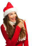 Beautiful woman in santahat pointing at copyspace Royalty Free Stock Images