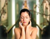 Beautiful woman at spa meditating eyes closed. Pretty brunette woman at spa with eyes closed meditating Royalty Free Stock Photo