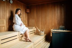 Beautiful woman in sauna pouring oils on hot stones royalty free stock photography
