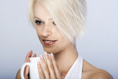 Beautiful woman savouring a cup of coffee. Beautiful young blond woman savouring a cup of coffee holding the cup in both hands with a thoughtful smile of Royalty Free Stock Photos