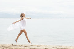 Beautiful woman with scarf feeling free on the beach. Full body portrait of beautiful woman with scarf feeling free on the beach with copy space Royalty Free Stock Photography