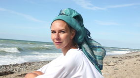 Beautiful woman sitting on the beach and smiling at camera. Beautiful woman with scarf wrapped around her head sitting on the beach and smiling at camera stock video footage